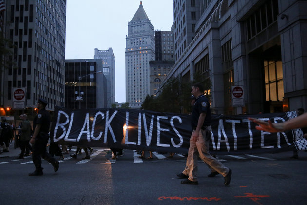 """Policemen walk on the sidelines as protesters hold a sign which states """"Black Lives Matter,"""" during a march against police brutality in Manhattan, New York, U.S., July 9, 2016. REUTERS/Bria Webb"""