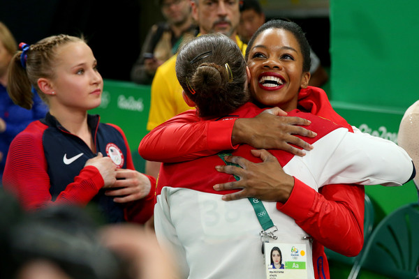 Aliya Mustafina of Russia is congratulated by Gabrielle Douglas of the United States on winning the gold medal after the Women's Uneven Bars Final on Day 9 of the Rio 2016 Olympic Games at the Rio Olympic Arena on August 14, 2016 in Rio de Janeiro, Brazil.