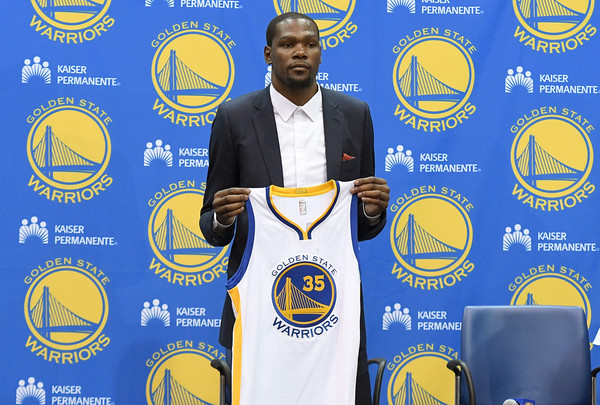 Kevin Durant #35 of the Golden State Warriors poses with his new jersey during the press conference where he was introduced as a member of the Golden State Warriors after they signed him as a free agent on July 7, 2016 in Oakland, California.