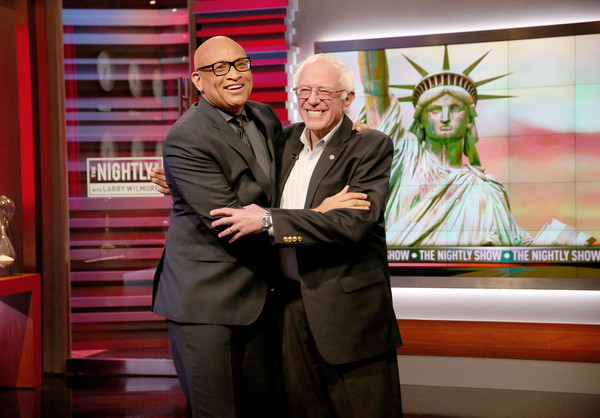 """Host Larry Wilmore (L) and Presidential Candidate Senator Bernie Sanders pose as he makes his fourth appearance on Comedy Central's """"The Nightly Show With Larry Wilmore"""" on April 13, 2016 in New York City."""