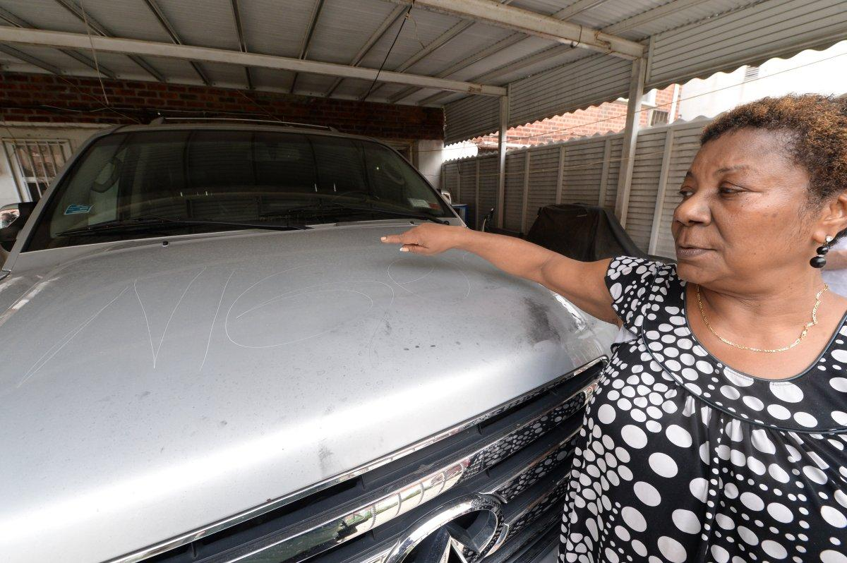 Julie Dorneval points to a mispelled racist scrawl on the hood of her car in Canarsie, Brooklyn, on Monday. (TODD MAISEL/NEW YORK DAILY NEWS)