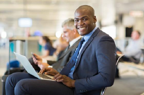 black-male-business-person-at-airport-laptop