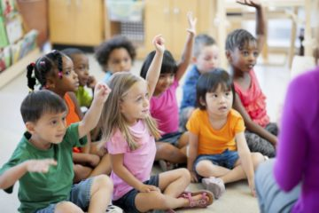 Preschool children raise their hands in class. (Vetta/Getty Images)