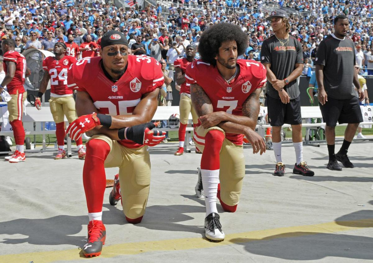 Colin Kaepernick, joined by teammate Eric Reid, continues his protest in Charlotte on Sunday. (MIKE MCCARN/AP)