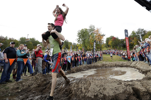 Jessica Keefe, celebrates after her husband, Michael Keefe, of Madbury, N.H., made it through the mud pit during the North American Wife Carrying Championship, Saturday, Oct. 8, 2016, at the Sunday River Ski Resort in Newry, Maine. (AP Photo/Robert F. Bukaty)