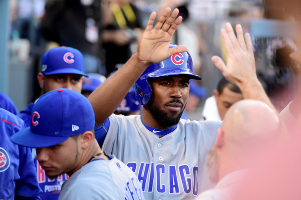 Dexter Fowler #24 celebrates in the dugout after he scores on a Anthony Rizzo #44 of the Chicago Cubs RBI double in the first inning against the Los Angeles Dodgers in game five of the National League Division Series at Dodger Stadium on October 20, 2016 in Los Angeles, California.