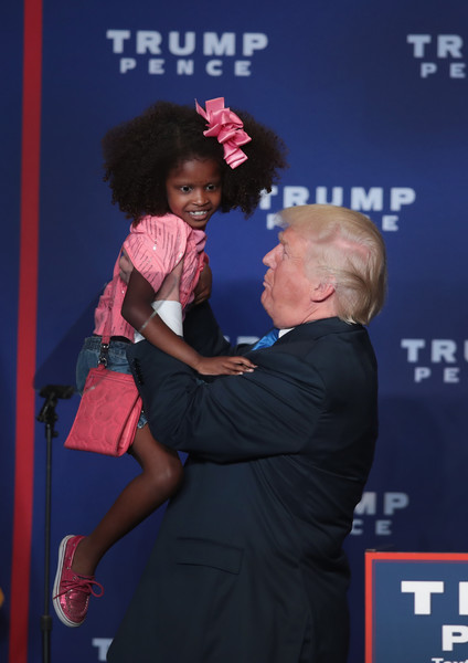 Republican presidential nominee Donald Trump holds a child while speaking at a campaign rally at the KI Convention Center on October 17, 2016 in Green Bay, Wisconsin.