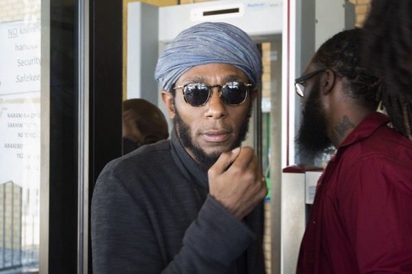 hip hop artist and actor, Yasiin Bey, popularly known as Mos Def, walks out of the Bellville Magistrates Court, refusing to take off his turban as requested by security, before being due to appear for contravening South African immigration laws, on March 8, 2016, in Cape Town (AFP)