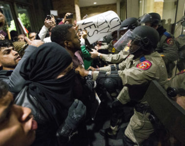 Law-enforcement officers push protesters out of the Texas A&M University student center on December 6.Photo: Brett Coomer/AP