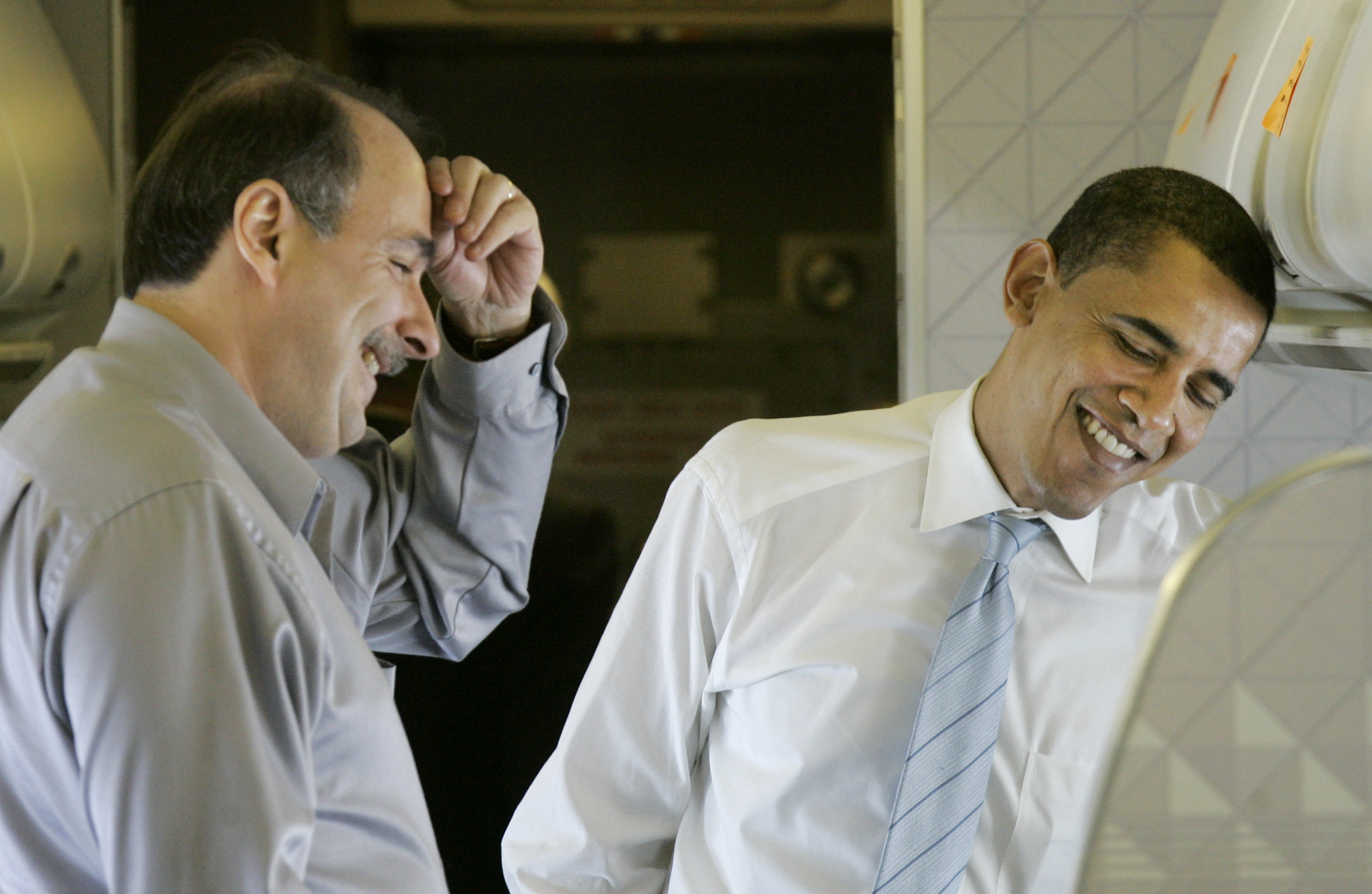 Democratic presidential hopeful Sen. Barack Obama, D-Ill., shares a laugh with his staff and Senior Campaign Advisor David Axelrod, left, during a flight between Chicago and East Rutherford, N.J., Monday, Feb. 4, 2008.(AP Photo/Charles Rex Arbogast)