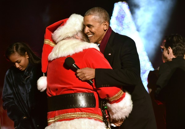 US President Barack Obama hugs and a man dressed as Santa Claus during the National Christmas Tree Lighting on the Ellipse of the National Mall in Washington on December 1, 2016. / AFP / Nicholas Kamm