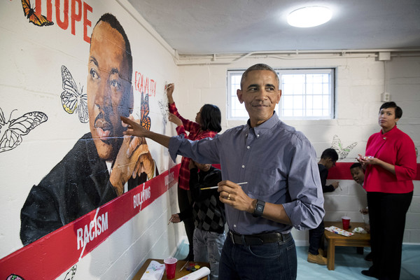 U.S. President Barack Obama (Front) and First Lady Michelle Obama (Back) help paint a mural depicting Martin Luther King Jr., as Mayor of Washington DC Muriel Bowser (R) looks on, at the Jobs Have Priority Naylor Road Family ShelterJanuary 16, 2017 in Washington, DC.