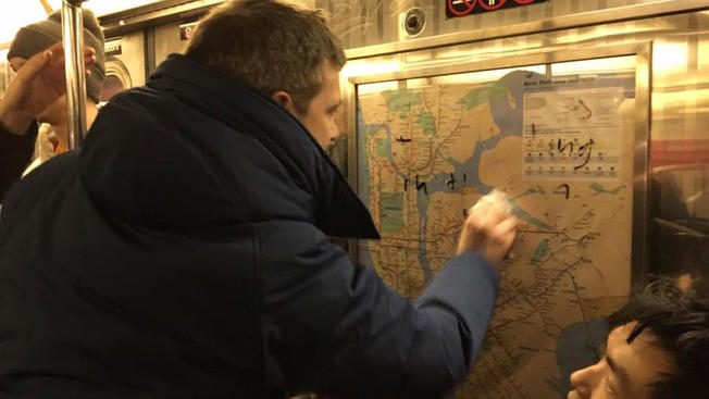 Subway passenger uses hand sanitizer and tissue to clean swastika image off of NYC train