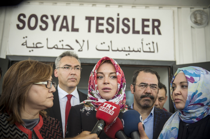 GAZIANTEP, TURKEY - OCTOBER 08: American actress Lindsay Lohan (C) speaks to press members with wearing a headscarf given by a Syrian woman, after her visit at a container town where Syrian refugees live in the Nizip district of Gaziantep in Turkey on October 08, 2016.      (Photo by Kerem Kocalar/Anadolu Agency/Getty Images)