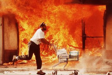 """(Published in special section May 12,1992) -- April 30, 1992-- The second day of the Riots on 3rd street I photographed this guy running past a burning Jon's market with a shopping cart full of diapers.  I affectionately call this image """"A Huggies Run""""."""