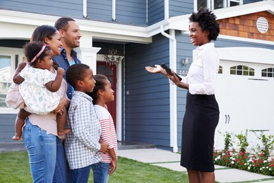 black family and black real estate agent outside of house
