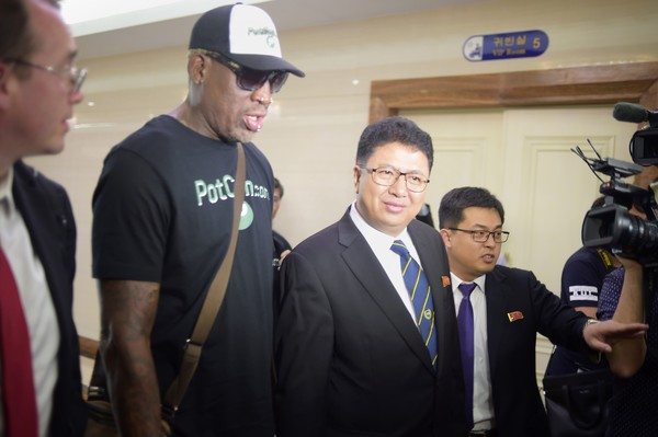 Flamboyant former NBA star Dennis Rodman (2nd L) of the US talks with Son Gwang-Ho (C), North Korea's vice minister for sports and culture, after his arrival at Pyongyang International Airport on June 13, 2017