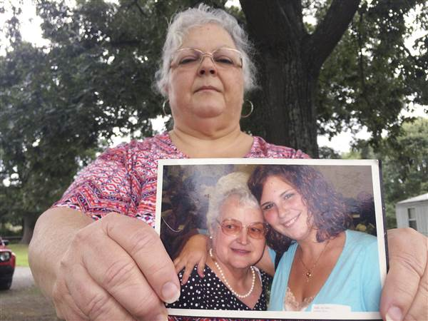 Susan Bro, the mother of Heather Heyer, holds a photo of Bro's mother and her daughter on Aug. 14, 2017, in Charlottesville, Va.