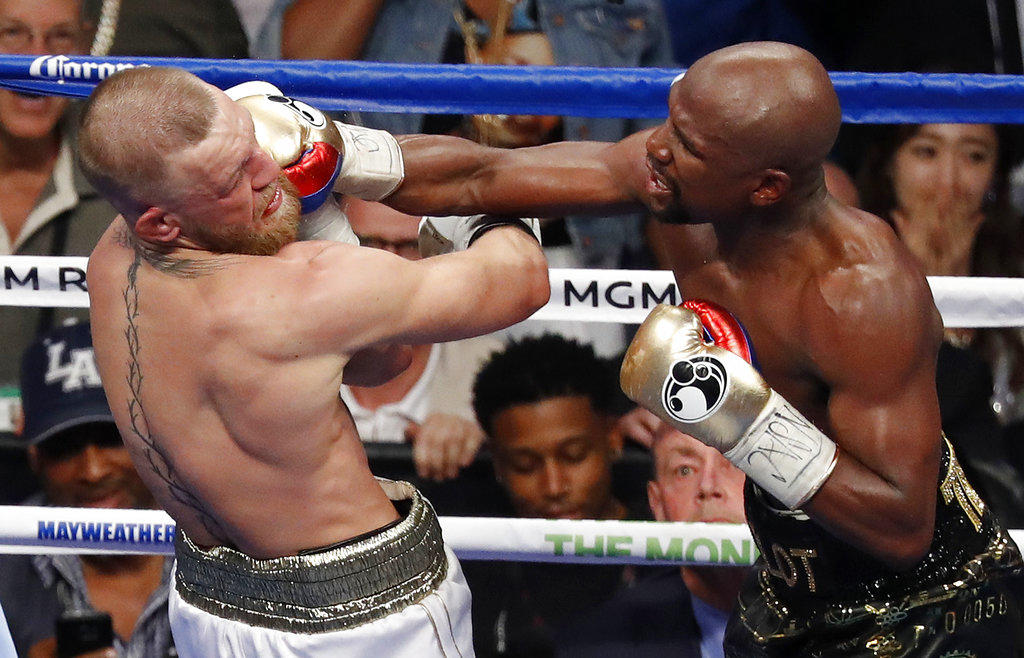 Floyd Mayweather Jr. hits Conor McGregor in a super welterweight boxing match Saturday, Aug. 26, 2017, in Las Vegas. (AP Photo/Eric Jamison)