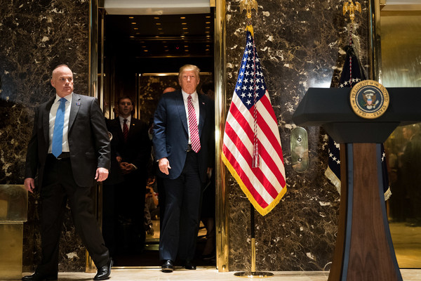 US President Donald Trump emerges from the elevator to deliver remarks following a meeting on infrastructure at Trump Tower, August 15, 2017 in New York City.