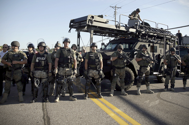 Police in riot gear watch protesters in Ferguson, Mo., Aug. 13, 2014. (Credit: AP/Jeff Roberson)