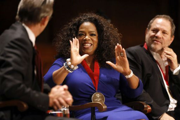 Actor, talk show host and philanthropist Oprah Winfrey, center, speaks with Glenn Hutchins, left, as film producer Harvey Weinstein, right, sits near moments after Winfrey received the W.E.B. Du Bois medal during ceremonies, Tuesday, Sept. 30, 2014, on the campus of Harvard University, in Cambridge, Mass. The Du Bois Medal is Harvard's highest honor in the field of African and African American Studies. Credit: (AP Photo/Steven Senne)