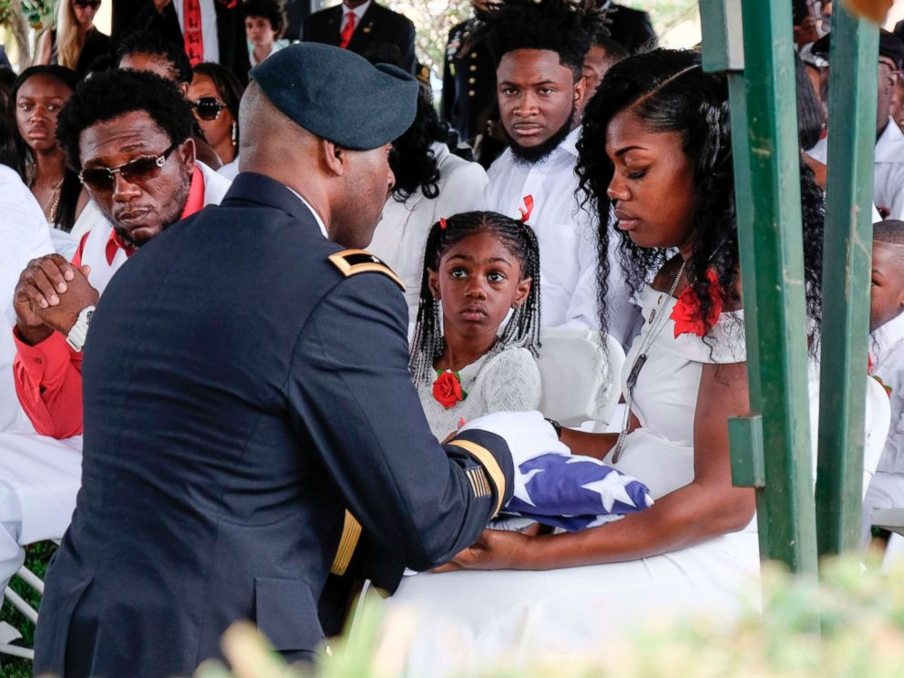 Myeshia Johnson is presented with a folded U.S. flag by a military honor guard member during the burial service for her husband U.S. Army Sgt. La David Johnson at the Memorial Gardens East cemetery, Oct. 21, 2017, in Hollywood, Fla.