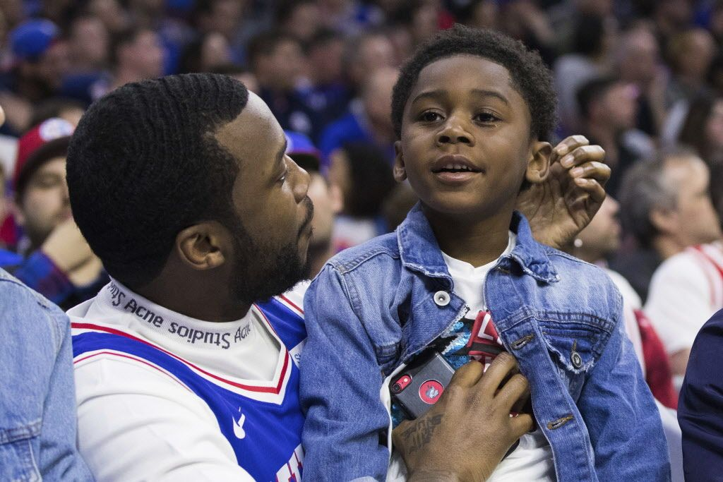 Rapper Meek Mill, left, looks on with his son, right, during the first half in Game 5 of a first-round NBA basketball playoff series between the Miami Heat and the Philadelphia 76ers, Tuesday, April 24, 2018, in Philadelphia. (AP Photo/Chris Szagola)