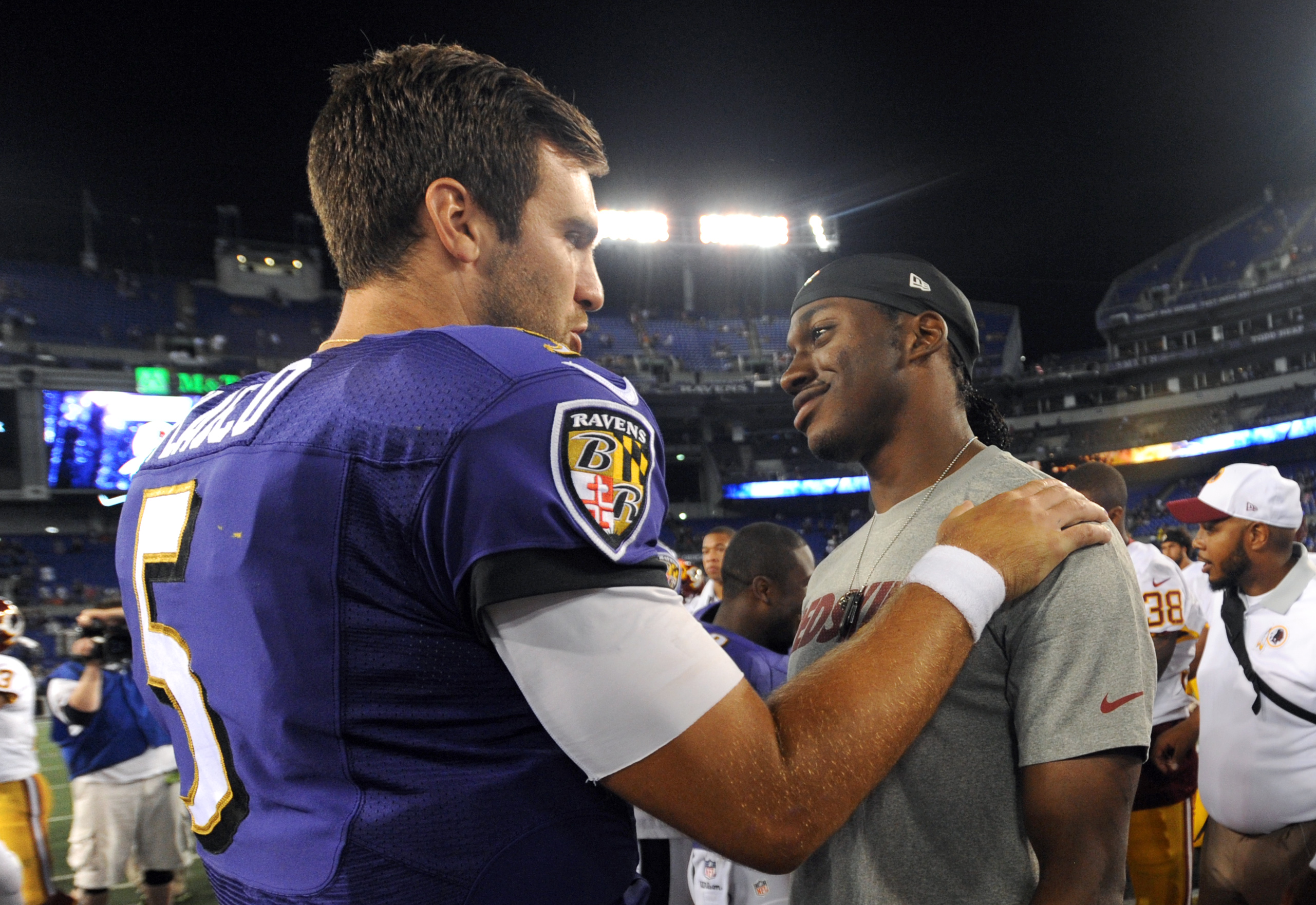 Baltimore Ravens quarterback Joe Flacco, left, chats with Washington Redskins quarterback Robert Griffin III after a preseason NFL football game, Saturday, Aug. 29, 2015, in Baltimore. (AP Photo/Gail Burton)