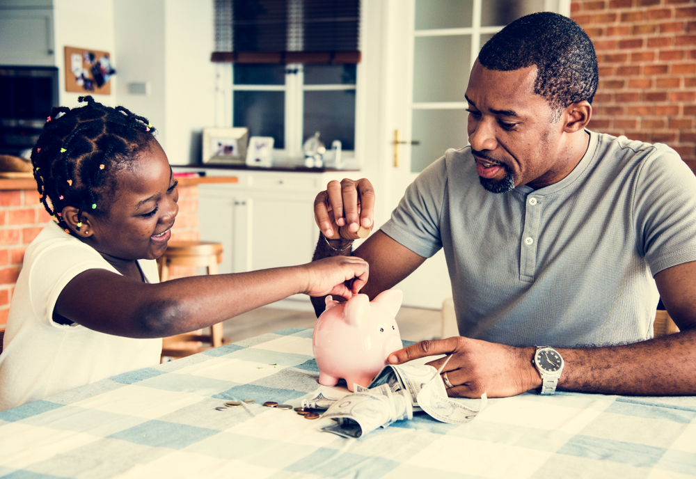 father and daughter with piggy bank at kitchen table