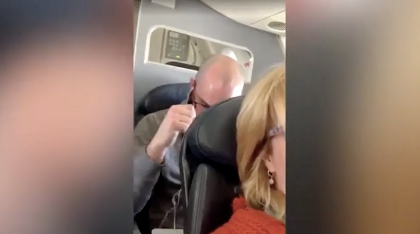 Man punches seat of woman in front of him on flight