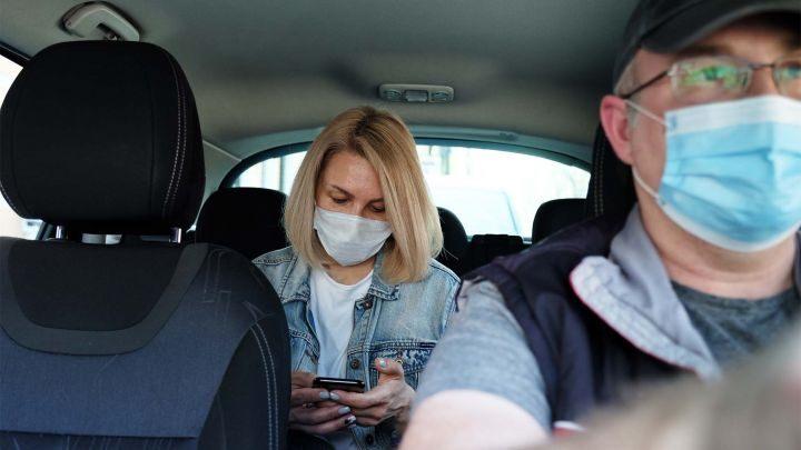 Uber - Coronavirus-woman passenger & male driver wearing facemasks (iStock)