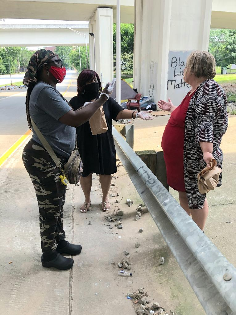 Cassandra McAllister & Angela Showell speaking to a homeless lady at Tent City