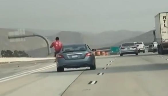 Man hanging outside car on driver side