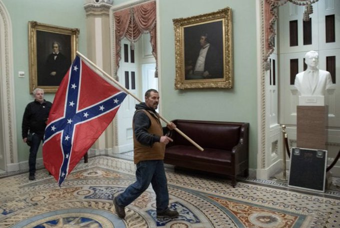 man storms capitol with confederate flag