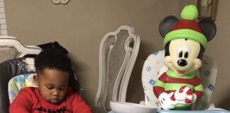 Toddler shares food with Mickey Mouse