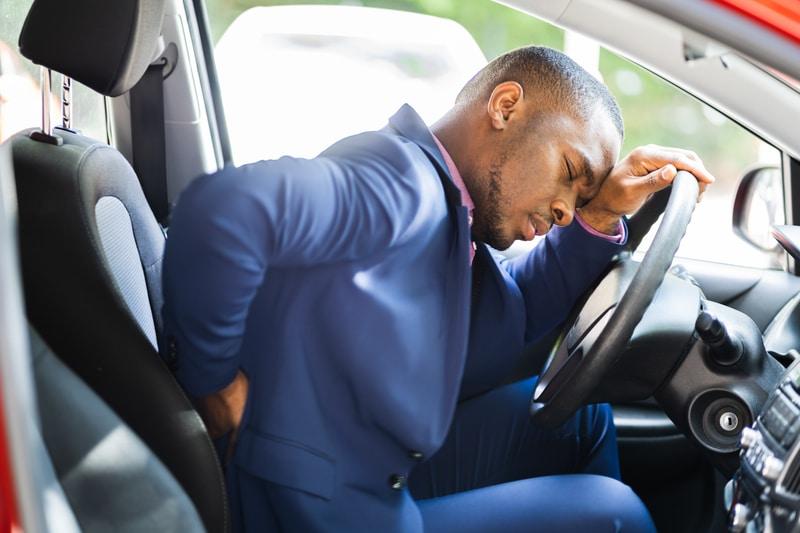 Man in car car - back pain - dreamstime_s_212685137 (1)