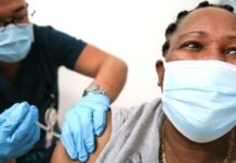 Black person (masked) getting vaccination / Getty