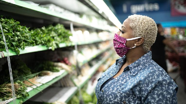 Woman wearing mask in supermarket - GettyImages-1218093780_header-1024x575