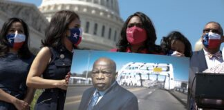 Rep. Terri A. Sewell (D-Ala.) holds a photo of the late congressman John Lewis (D-Ga.) at an event outside the Capitol on Aug. 24. (Anna Moneymaker/Getty Images)